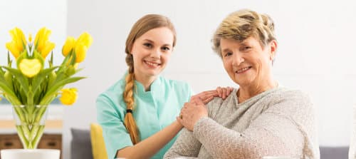 smiling old woman and caregiver